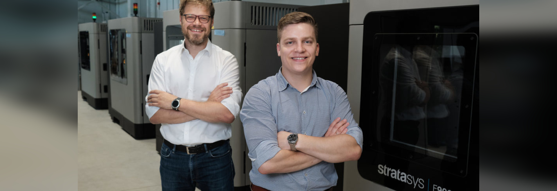 AM Craft co-founders Jānis Jātnieks (right) and Didzis Dejus in front of the service provider's four large-scale production-grade Stratasys F900 3D Printers
