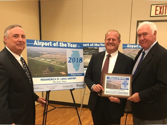 MidAmerica St. Louis Airport Director Tim Cantwell, St. Clair County Chairman Mark Kern and Rich Sauget, Chair of The Public Building Commission of St. Clair County pause for a photo by the signage...
