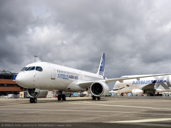 An Airbus A220-300 sits parked in front of an Airbus Beluga transport outside the manufacturer's Toulouse factory. (Photo: Airbus)