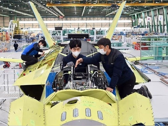 A handout photo released by KAI shows workers of Korea Aerospace Industries (KAI) assemble the first prototype of South Korea's indigenous fighter jet at its plant in the southeastern city of Sache...